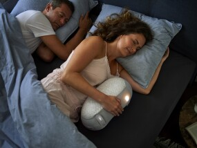 Woman hugging a Somnox Sleep Robot in bed with her partner